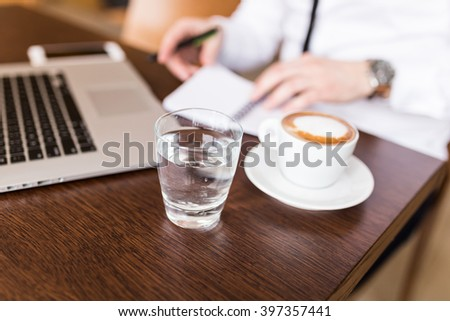 Businessman sitting at coffee shop working on laptop computer. Coffee, water and documents on table. Selective focus, depth of field - stock photo