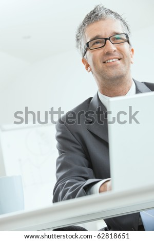 Businessman sitting at desk and working with laptop computer. Looking at camera, smiling.