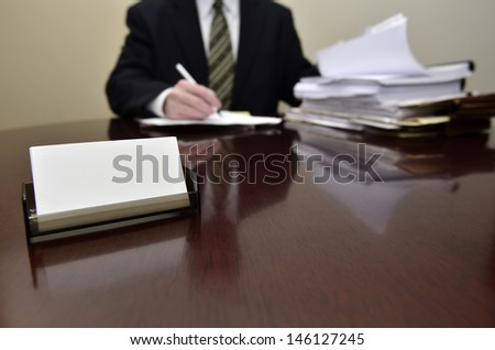 Businessman sitting at desk holding pen with files
