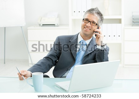 Businessman sitting at desk in bright office, talking on mobile phone and smiling. - stock photo