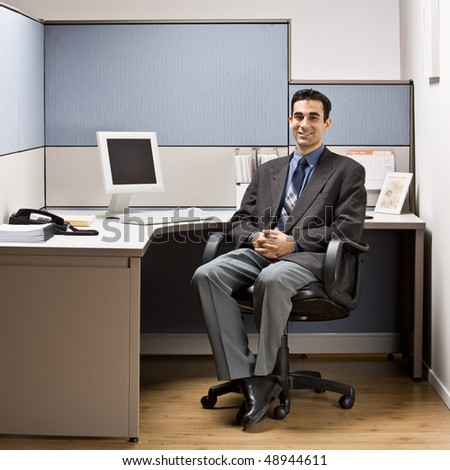 Businessman sitting at desk in cubicle - stock photo