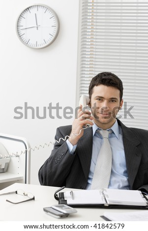 Businessman sitting at desk in office, talking on landline phone, smiling. - stock photo
