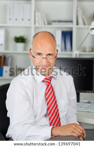 businessman sitting at desk, looking over his glasses