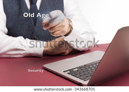 businessman sitting at desk pointing at screen gesturing old age pension planning wealth and security