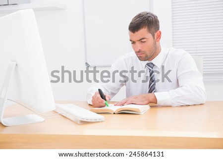 Businessman sitting at desk reading a book in his office