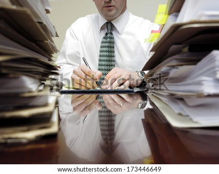 Businessman sitting at desk with pad of paper and piles files - stock photo