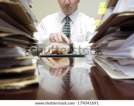 Businessman sitting at desk with pad of paper and piles files pointing watch