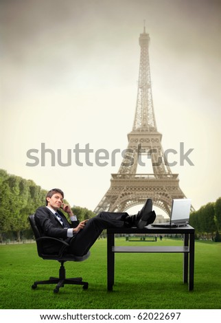 Businessman sitting at his desk in a park with Eiffel Tower on the background - stock photo