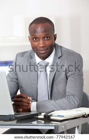 Businessman sitting at his desk in office - stock photo