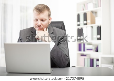Businessman sitting at his desk in the office looking at his laptop with a wry expression grimacing as he reads information on the screen - stock photo