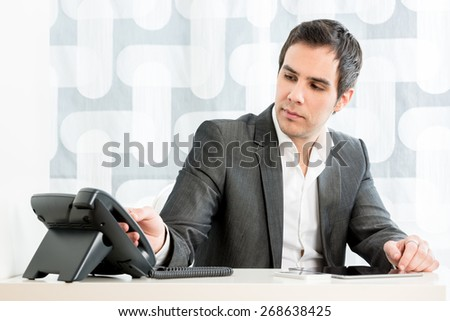 Businessman sitting at his desk in the office reaching for the telephone with his hand on the handset as he makes or answers a call in a communication concept. - stock photo