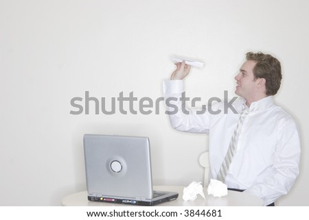 Businessman sitting at his desk throwing a paper airplane for his own amusement with a laptop on his desk