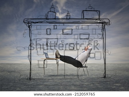businessman sitting at his desk trying to free his imagination - stock photo