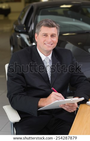 Businessman sitting at his desk while writing on clipboard at new car showroom - stock photo