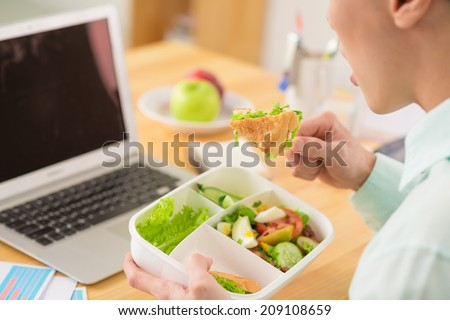 Businessman sitting at his table and eating salad for lunch - stock photo