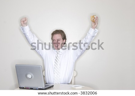 businessman sitting at his table with his laptop and hands outstretched and in the air for success while holding his sandwich