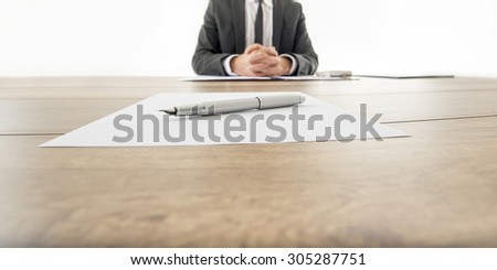 Businessman sitting at his wooden office desk with contract infront of him and another contract opposite to him with a pen waiting to be signed by employee or business partner.  - stock photo