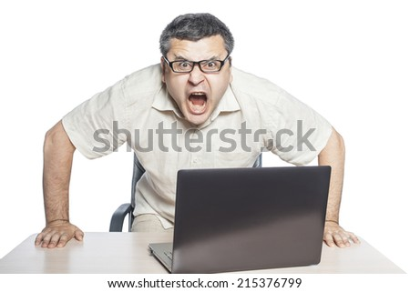 Businessman sitting at laptop and shouting, crisis and stress at work. - stock photo