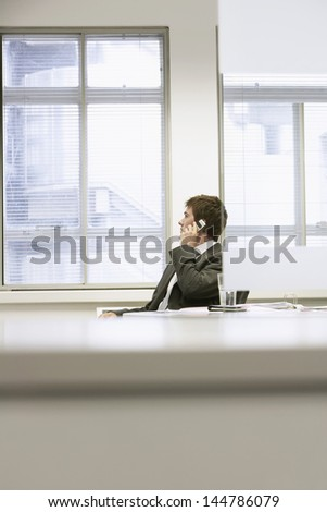 Businessman sitting at office desk and using cellphone