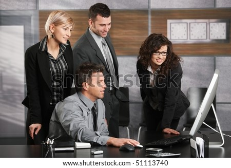 Businessman sitting at office desk, looking at screen together with colleagues, smiling. - stock photo