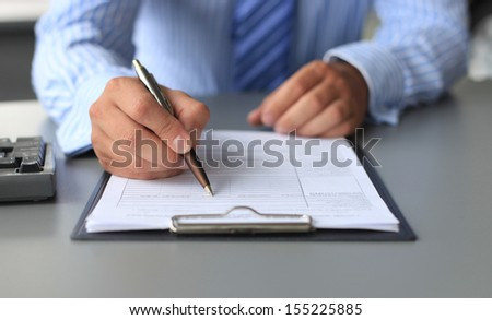 Businessman sitting at office desk signing a contract