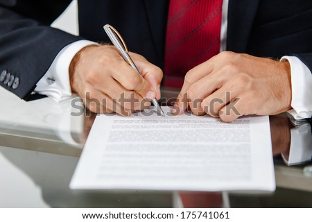 Businessman sitting at office desk signing a contract.
