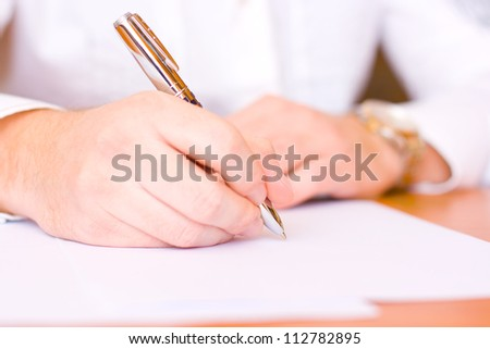 Businessman sitting at office desk signing a contract - focus on right hand with a pen - stock photo