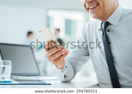 Businessman sitting at office desk using a touch screen smart phone, hands close up, office interior and business people on background, selective focus - stock photo