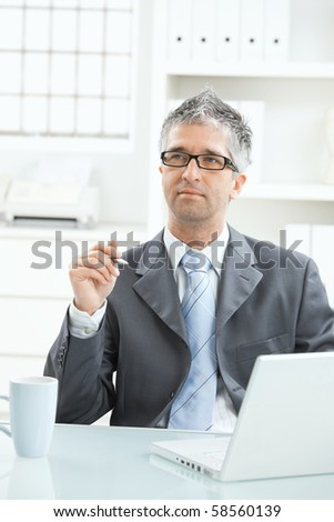 Businessman sitting at office desk working on laptop computer.