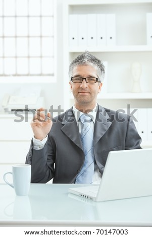 Businessman sitting at office desk working on laptop computer.?