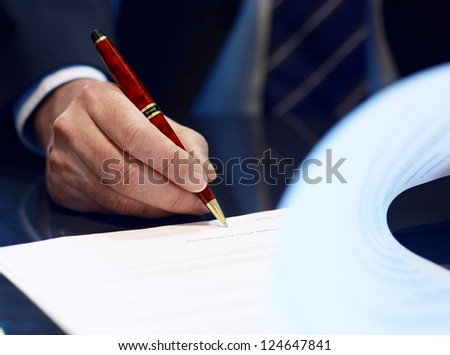 Businessman sitting at shiny office desk signing a contract with noble classic pen - stock photo