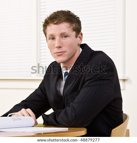 Businessman sitting at table - stock photo