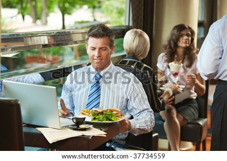 Businessman sitting at table in cafe, eating club sandwich and  using laptop computer. Waiter serving sweets in the background. - stock photo