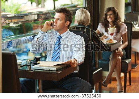 Businessman sitting at table in cafe, reading newspaper and talking on mobile phone. - stock photo
