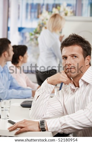 Businessman sitting at table in meeting room at office, looking at camera.