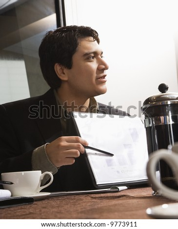 Businessman sitting at table pointing to bar graph.