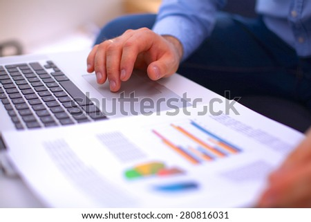 Businessman sitting at table with laptop and documents - stock photo
