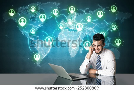 Businessman sitting at table with social media connection symbols on the world map  - stock photo