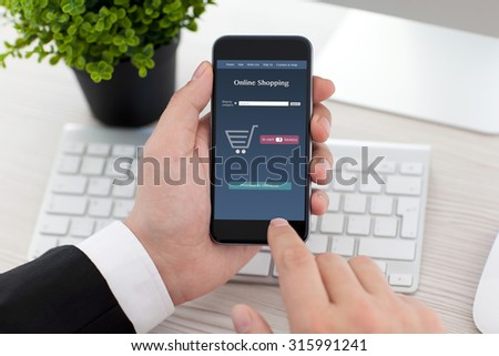 businessman sitting at the desk in office and holding phone with app online shopping on the screen - stock photo