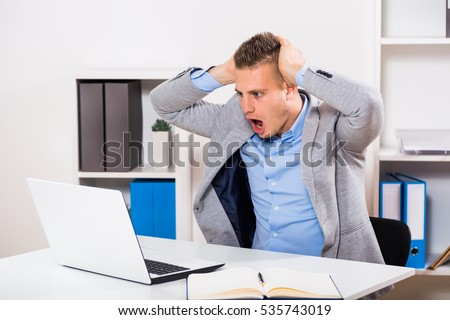 Businessman sitting at the table and looking at his laptop in panic.Businessman in panic looking at laptop