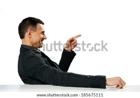 Businessman sitting at the table and pointing at copyspace - stock photo