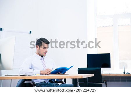Businessman sitting at the table and reading document in office - stock photo