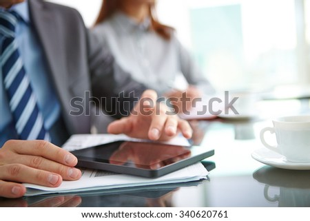 Businessman sitting at the table and using touchpad - stock photo