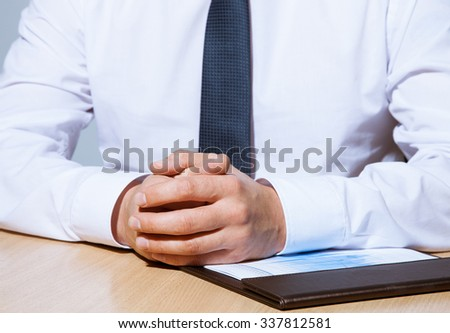 Businessman sitting at the table, closeup shot - stock photo