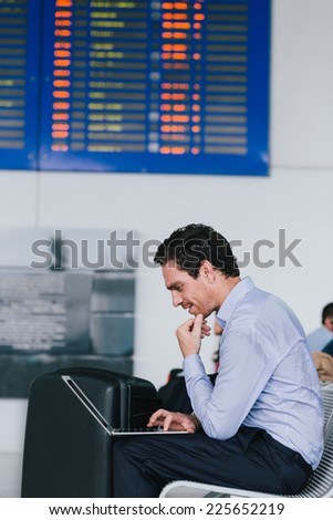 Businessman sitting at the waiting room of the airport and using laptop - stock photo