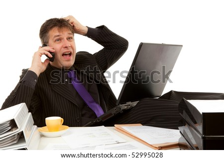 Businessman sitting behind desk is in despair, pulling his hair, over white background