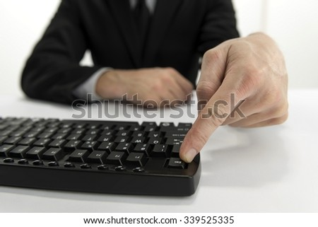 Businessman Sitting Behind the Table and Pressing Escape Key on the Keyboard