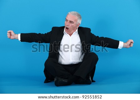 businessman sitting cross-legged and stretching - stock photo