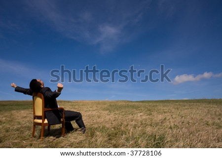 businessman sitting in a chair in outdoor looking to the field - stock photo