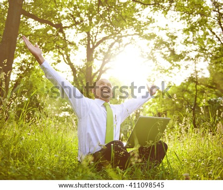 Businessman sitting in a forest with his laptop. - stock photo